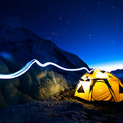 A climber's headlamp traces the route into the First Ascent Pantheon Tent at Advanced Basecamp on Mount Everest.