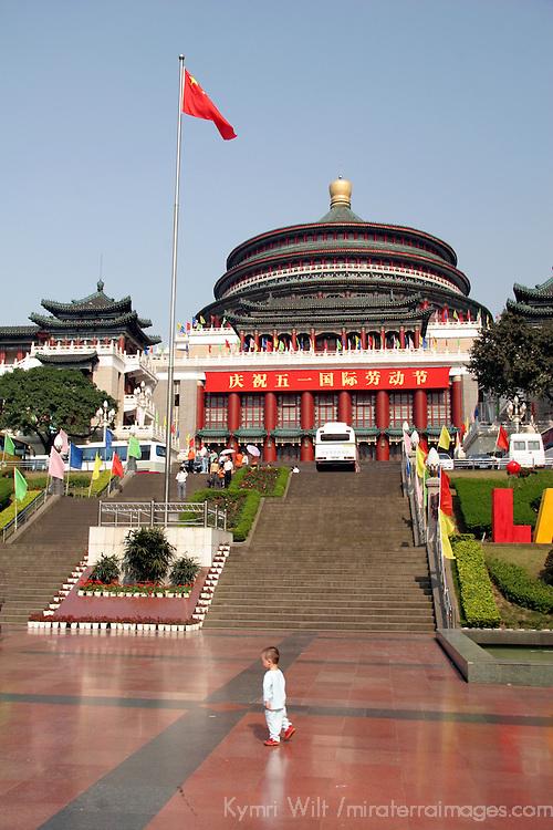 Asia, China, Chongqing.  A small toddler walks across a vast plaza.