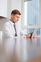Mid adult businessman using tablet computer at kitchen table