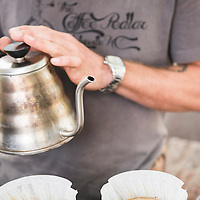 Ryan Prentiss pouring hot water over coffee grinds. Ryan is the owner of the Coffee Pedlar, a mobile bicycle coffee cart that he often parks at Pritchard Park in downtown Asheville, North Carolina, where he serves high quality coffee to customers.