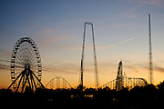 Sunset view of the Darien Lake theme park, with roller coasters and a Ferris wheel silhouetted against the sky. Darien Lake is close to Buffalo, in New York.