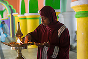 Nagore. Dargah shrine - woman at lamp.