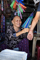 An elderly shopkeeper ties a wrist band on the arm of a teenage boy who has just purchase it, in Hoi An, Vietnam