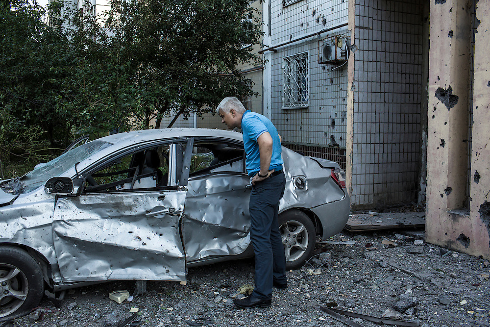 A man looks at a car destroyed by a suspected grad rocket strike outside an apartment building on Tuesday, July 29, 2014 in Donetsk, Ukraine.