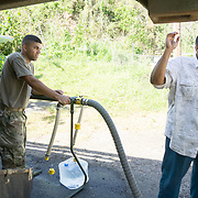 OCTOBER 25 - UTUADO, PUERTO RICO - <br /> SPC Andrea Bertarello fills up 5 gallon jugs from a water truck with 2,000 gallons of potable water parked near a baseball park in Utuado for resident Jose Santiago Alvarez. Troops from Fort Bragg, NC, are using a water filtration system to purify water from the nearby Lago Dos Bocas.<br /> (Photo by Angel Valentin/Freelance)
