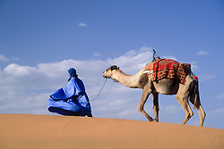 Africa, Morocco, Tinfou (near Zagora).Man in traditional dress leading camel on sand dunes.MR