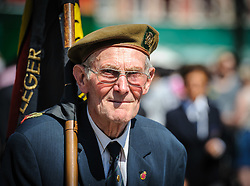 A World War 2 veteran marches behind a band in the Grote Markt, Bruges, Belgium as part of the celebrations of Belgium's National Day on 22nd July.<br /> <br /> (c) Andrew Wilson | Edinburgh Elite media