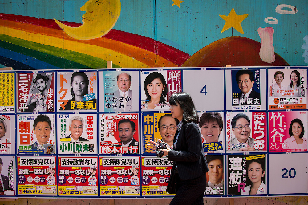 TOKYO, JAPAN - JULY 7 : Woman walks past at campaign posters with pictures of candidates for the 2016 Upper House election in Tokyo, Japan on Thursday, July 7, 2016.  The July 10 Upper house election is the first nation-wide election in Japan after government law changes its voting age from 20 years old to 18 years old.(Photo by Richard Atrero de Guzman/NURPhoto)