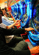 """Customers play """"pachinko,"""" a game sometimes referred to as Japanese pinball, at a pachinko parlor in Tokyo, Japan. Pachinko is a game unique to Japan, in which players first purchase small metal balls that are then inserted into the machine with the purpose of attempting to win more balls. Accumulated balls can be exchanged for prizes such as vouchers, tokens (usually small pieces of gold in plastic cases) or a range of goods. There is also a method of exchanging the winnings for cash, though this is illegal. Despite the fact that gambling is officially illegal in Japan, there are some 13,000 pachinko halls, known as """"pachinko parlors"""", scattered throughout the country, mostly located near to main line railway stations, but some are found in the middle of the countryside, their neon signs lighting up the paddy fields near which they stand. Some of the larger ones host several hundred playing machines. There are also hundreds of pachinko magazines guiding readers the key to winning the game, and there are even those people who make a living from the game. Known as """"pachi-puro,"""" or professional pachinko players, the best of these players can earn around 600,000 yen (US$6,000) per month from the game.  .."""