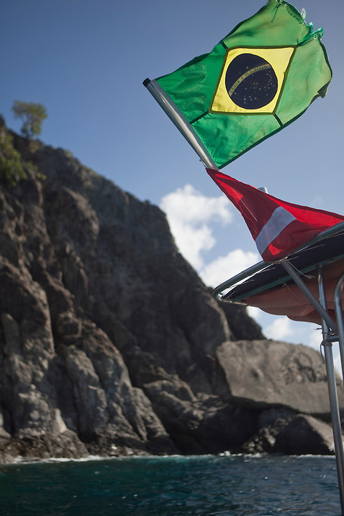 Brazilain flag waving on the stern of a boat at Fernando de Noronha island, Brazil.