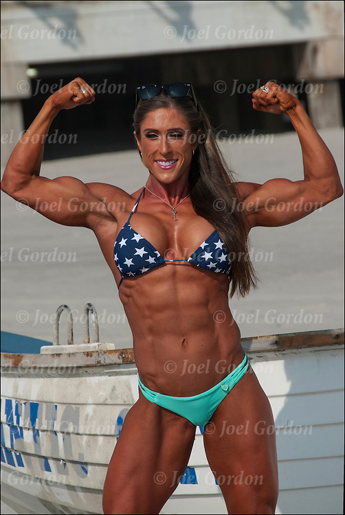 Professional female bodybuilder doing specified poses on the beach for photographer.  <br /> <br /> In competitive amateur and professional bodybuilding, bodybuilders appear in lineups doing specified poses, and later perform individual posing routines, for a panel of judges who rank competitors based on criteria such as symmetry, muscularity and conditioning.