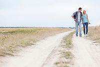 Full length of young hiking couple standing on trail at field
