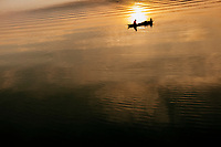 A fisherman drifts across quiet waters at dusk on Tuyen Lam lake in Dalat, in the Central Highlands of Vietnam.