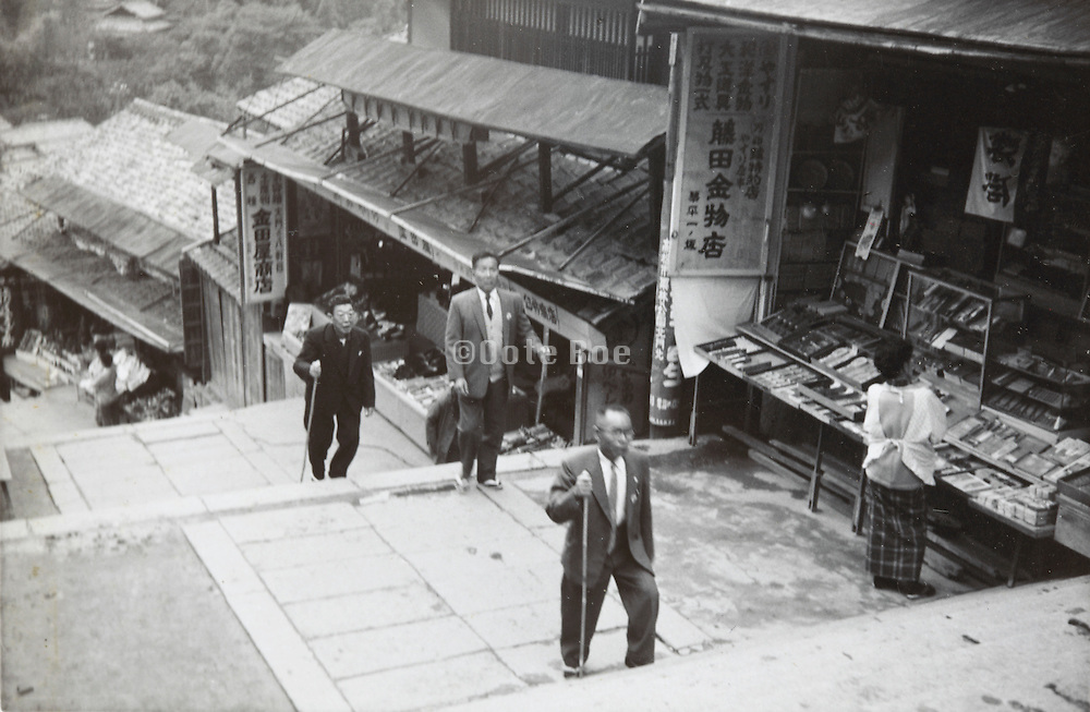 Japanese men on an touristic trip visiting a temple or shrine 1960s
