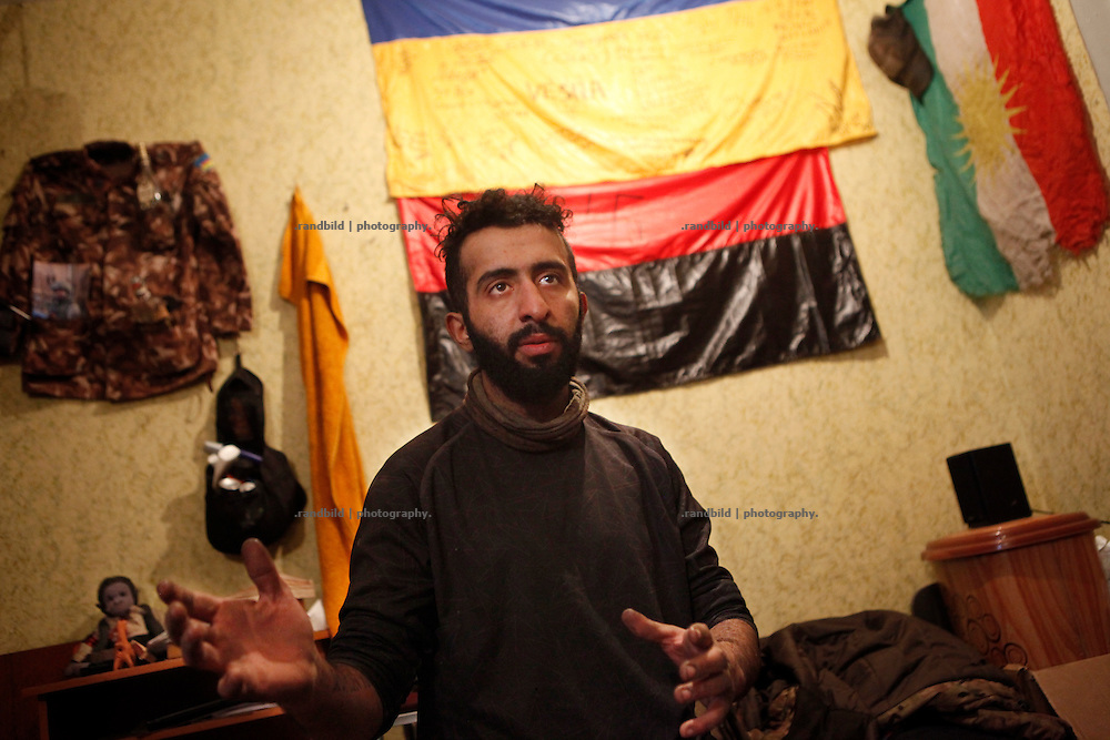Ben gestures in his room, the wall behind him full of memorabilia like the jacket from a dead comrade, an ukrainian flag, the peshmerga flag from Iraq and a Prawy Sector flag (red-black) with a swastika on it.<br />