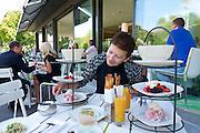 Vienna, Austria. Steirereck breakfast at the Meierei im Stadtpark.<br /> Marinierte Beeren mit Baiser & Passionsfrucht (Marinated Berries with Meringue and Passionfruit), Beinschinken mit Kren & Weizenknusper (Gammon Ham with Fresh Horseradish & Panini), Bauern–Ei im Glas mit Rahm & gehobelter Gänseleber (Soft–Boiled Egg with Sour Cream & Foie Gras), Saiblings–Tatare mit Sprossensalat (Char Tartare with Bean Sprouts and Black Radish)