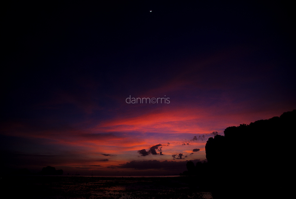 Wispy, pink clouds at sunset with moon overhead, Tonsai Beach, Thailand
