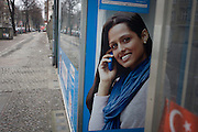 The poster of an Asian-looking model advertisies a telecoms company services in an internet store window.in Wedding, a north-western district of Berlin.