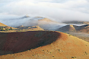 Clouds flowing over cinder cones on the flanks of dormant volcano Mauna Kea, on the Big Island of Hawaii.