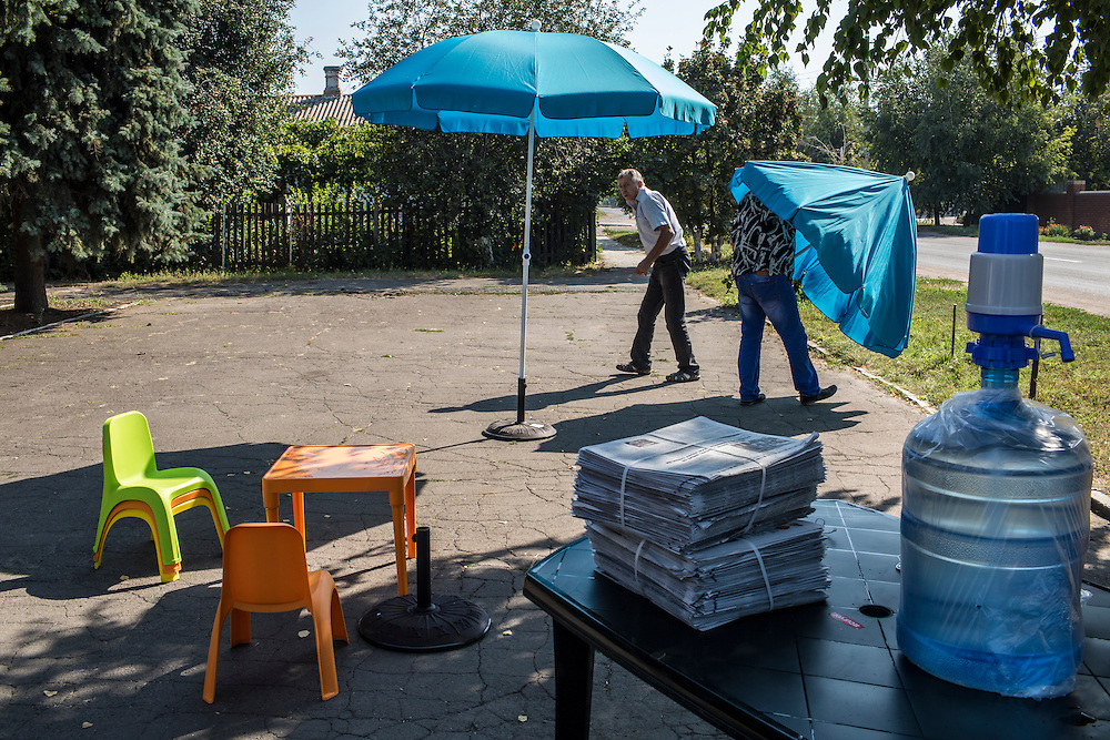 SARTANA, UKRAINE - AUGUST 29, 2015: Workers set up umbrellas to provide shade during distribution of humanitarian aid in Sartana, Ukraine. The village of Sartana, on the northeastern outskirts of Mariupol, has been relatively close to the front line between Ukrainian and pro-Russian rebel forces, with many incidents of shelling damaging homes and injuring or killing civilians. CREDIT: Brendan Hoffman for The New York Times