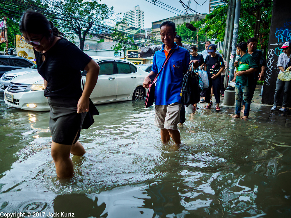 27 MAY 2017 - BANGKOK, THAILAND: Pedestrians on a sidewalk flooded by monsoonal rains along Ekkamai Road in suburban Bangkok. The rainy season in Bangkok usually starts in mid-June but started almost a month early this year. There have been daily thunderstorms and localized flooding throughout central Thailand since the middle of May.     PHOTO BY JACK KURTZ