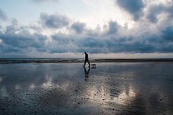 © Licensed to London News Pictures. 26/03/2014<br /> <br /> Redcar, Cleveland, United Kingdom<br /> <br /> Paul Markham from Redcar walks his dog over wet sand on the beach at Redcar, Cleveland at first light.<br /> <br /> Photo credit : Ian Forsyth/LNP