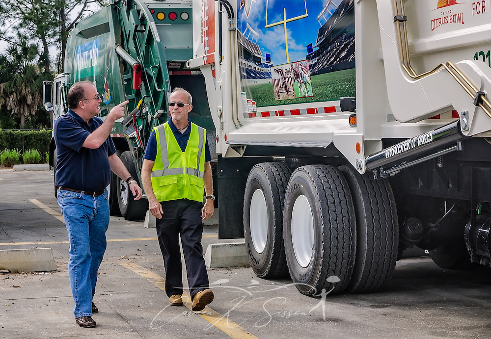 "Tim Dolan, Waste Pro Regional Vice President for Central Florida, points out a new truck wrap to operations specialist Terry Grady as they walk past a Mack Truck at Waste Pro, March 18, 2016, in Sanford, Florida. Waste Pro offers waste and recycling services to more than two million residential customers and more than 40,000 businesses in Alabama, Florida, Georgia, South and North Carolina, Louisiana, Mississippi, and Tennessee. The company has committed to ""going green"" by implementing a number of green initiatives, including using CNG (Clean Natural Gas) in its trucks, recycling more waste instead of sending it to landfills, and powering its regional headquarters throuh solar energy. (Photo by Carmen K. Sisson/Cloudybright)"