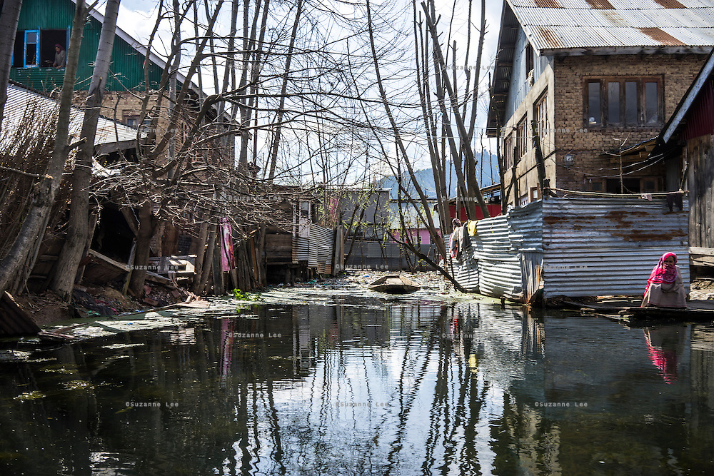 A woman squats in the sun amidst destroyed properties on the Dal Lake, Srinagar, Jammu and Kashmir, India, on 25th March 2015. Nearly 2500 villagers including Srinagar, the capital of the state of Jammu and Kashmir, was devastated by severe floods and landslides in September 2014 the worst in 60 years, displacing millions of people, many of them children. Photo by Suzanne Lee for Save the Children