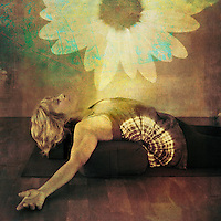 Mature woman resting on a yoga bolster experiencing a bloom of healing light.<br />