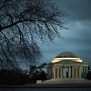 The Jefferson Memorial under winter clouds before sunrise, with some of the branches of a cherry tree at left.