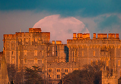 © Licensed to London News Pictures. 10/01/2020. Windsor, UK. The full moon rises into cloud over Windsor Castle which is bathed in the glow of the sunset. January's full moon, known as the Wolf Moon, is fully at it's peak at 19:21 hrs tonight. Photo credit: Peter Macdiarmid/LNP
