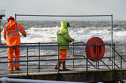 &copy; London News Pictures. 08/12/2017. Aberystwyth, UK.<br /> Local authority workers erect safety barriers to prevent the public from accessing the seaside jetty and more huge waves crash against the shore. The southern edge of Storm Caroline, with winds gusting between 40 and 60 mph, is still impacting on the harbour lighthouse  sea defences  in Aberystwyth, Ceredigion , west Wales UK. Photo credit: Keith Morris/LNP