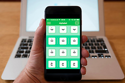 Using iPhone smartphone to display arabic alphabet in an Arabic language learning a app.