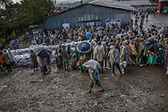 Rural highlander families gather in a muddy compound on the edge of Lalibela for the distribution of wheat by the US gov't aid organization, USAID.  International aid organizations and governments are hoping to stave off famine by distributing grain in the Ethiopian Highlands as the worst drought in decades have given way to unusually heavy rains, which also threaten harvests and food security.   Mush of this region of the Ethiopian Highlands have been categorized by USAID as having a high or extreme chance of food insecurity.  Lalibela, Ethiopia.
