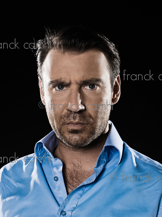 caucasian man unshaven frown angry portrait isolated studio on black background