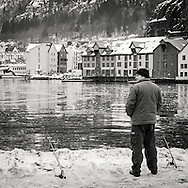 Man fishing of the pier in central Bergen at winter