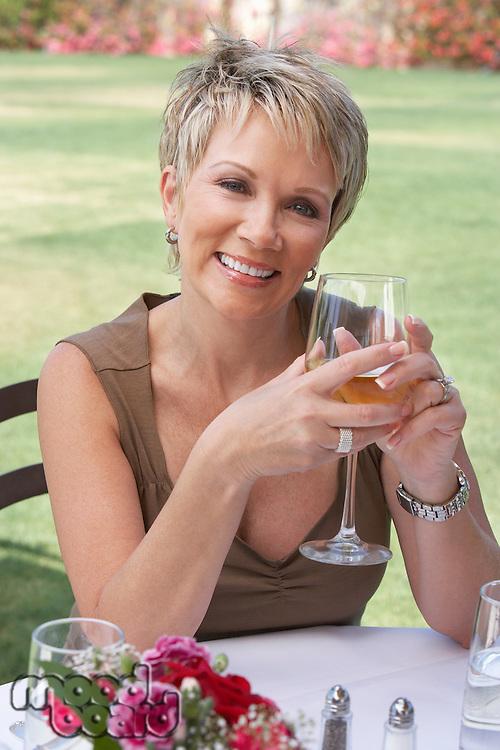 Smiling Woman Enjoying a Glass of White Wine