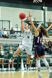 06 December 2017:  Ashley Schneider lays it up passing by Devin Kyler during an NCAA women's basketball game between the Wheaton Thunder and the Illinois Wesleyan Titans in Shirk Center, Bloomington IL