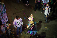 A young woman on Bourbon Street teases people in a balcony as others look on from street-level. Mardi Gras 2013 in New Orleans.