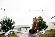 Keya swings on a homemade hammock at her home on the Rosebud Indian Reservation