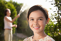 Girl smiling head and shoulders mother watering garden