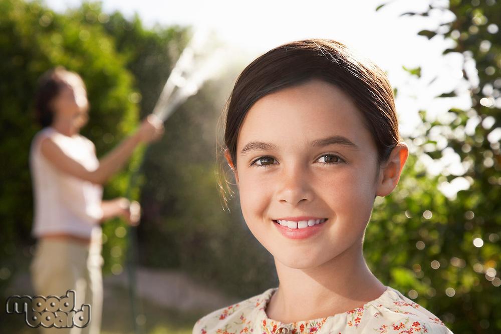 Girl smiling head and shoulders mother watering garden
