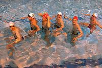 Equipe masculine de natation synchronisée photographiée à l'entrainement avec leur coach en mai 2004 dans une piscine parisienne.