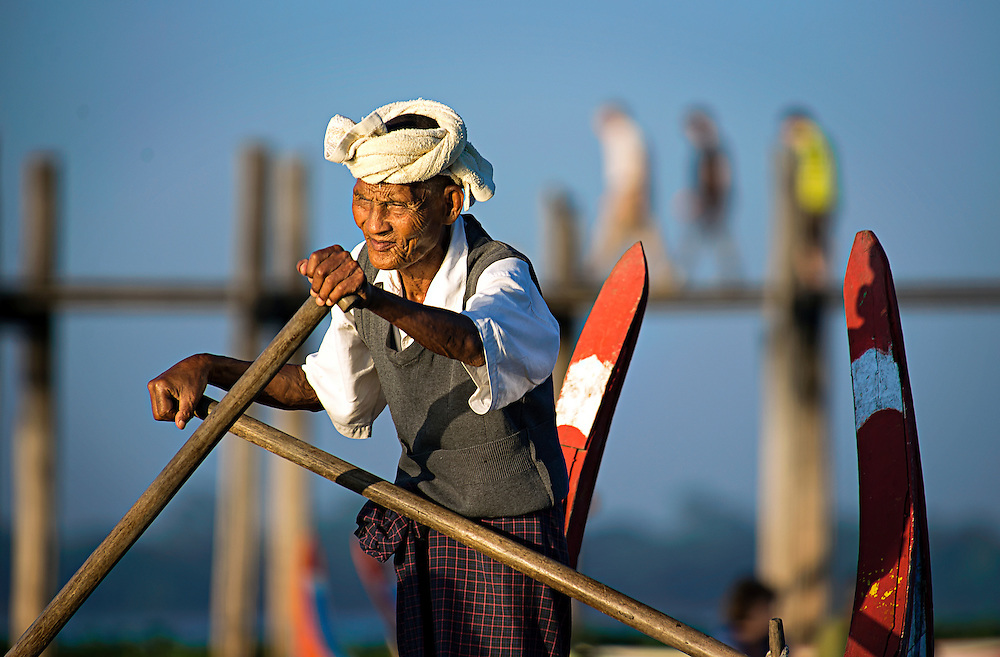 A boatman rowing near the bridge at U-Bien in Myanmar.