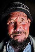 Khadim, 72, is portrayed at the entrance of his cave. During the years Khadim's family has been able to build some walls around the original cave and make it a more comfortable home, in Bamyan, central Afghanistan, an area mostly populated by Hazaras. A historically persecuted minority (15%) due to more lenient Islamic faith and characteristic 'Eastern' lineaments, Hazaras constitute the 70% of Bamyan's population.