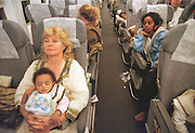8/8/01 -- (PHOTO BY MIKE FENDER) w/ story, slug: AFRICA, file: 62040 // Cheryl Carter-Shotts, left, sleeps with Beza on her lap on the long 17 hour trip from Ethiopia to Newark. Etagegen Kilpack, 20, upper right, rests as well after getting babies to sleep. Kilpack was adopted out of Ethiopia five years ago and now lives in Utah. She returned to help escort children on the trip.