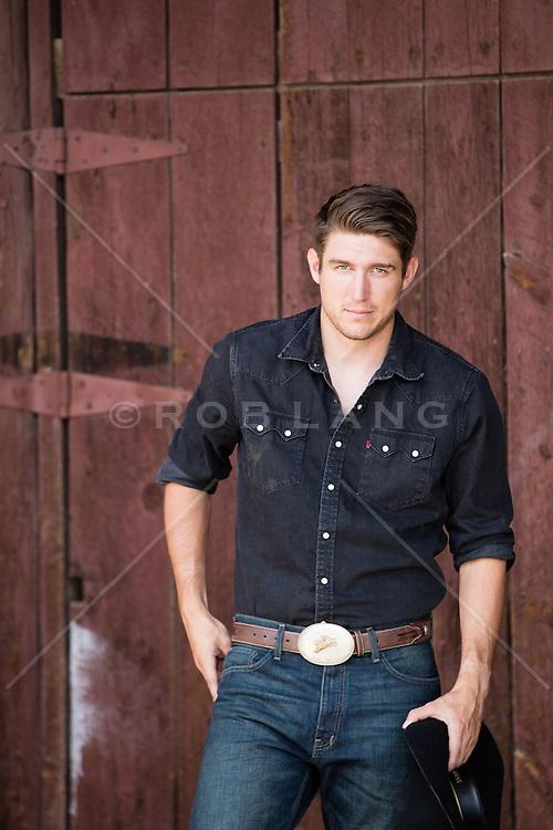 sexy cowboy by a rustic barn