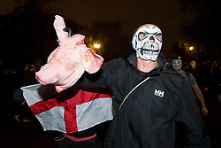 © Licensed to London News Pictures. 05/11/2015. London, UK. A masked demonstrator carrying a real pigs head during An anti-capitalist  protest organised by the group Anonymous outside Parliament in Westminster on bonfire night 05, November 2015. Bonfire night, also known as Guy Fawkes night, is an annual commemoration of when Guy Fawkes, a member of the Gunpowder Plot, was arrested for attempting to blow up the House of Lords at parliament.   Photo credit: Ben Cawthra/LNP
