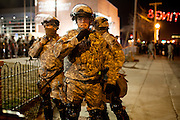 A National Guard MP adjusts his helmet strap as protestors being to pour into the street in front of the Ferguson police station. Large numbers of demonstrators took to the streets after a grand jury failed to indict Officer Darren Wilson for the death of Michael Brown Jr.