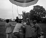 Dew Mighty Minerals Hot Air Balloon.   (H15)..1974..07.08.1974..08.07.1974..7th August 1974..The launching of the Dew Mighty Minerals hot air balloon,took place in Tullamore,Co Offaly last night,as part of the Tullamore Festival Week. The balloon was piloted by Mr Wilf Woollett,a veterinary surgeon from Loughrea,Co Galway and his co-pilot was Kevin Haugh. Miss Rosemary Mannion,the Offaly Rose of Tralee contestant sent the balloon on its way by popping a bottle of Champagne over it.  The balloon itself has a capacity of 56,000 cubic feet,is 60ft high and 50ft wide. It is made from nylon/polyproplene. The basket is 2ft square by 3ft high and carries two people,it is attached to the balloon by steel cables..Wilf Woollett has piloted the balloon in the U.S. and Britain and is a member of the Dublin Balloon Club...Wilf Woollett is pictured having a drink of Champagne as his amused co-pilot, Kevin Haugh looks on.